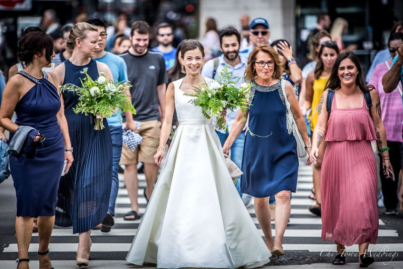 Bride walking with bridesmaids on street of Chicago