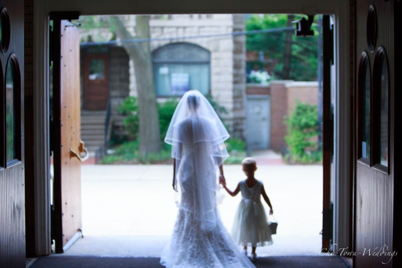 Bride with the flower girl holding hands walking from the church
