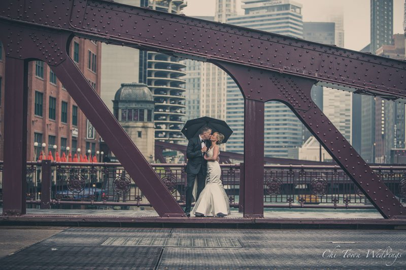 Bride and Groom posing at Lasalle Street Bridge with umbrellas in the rain