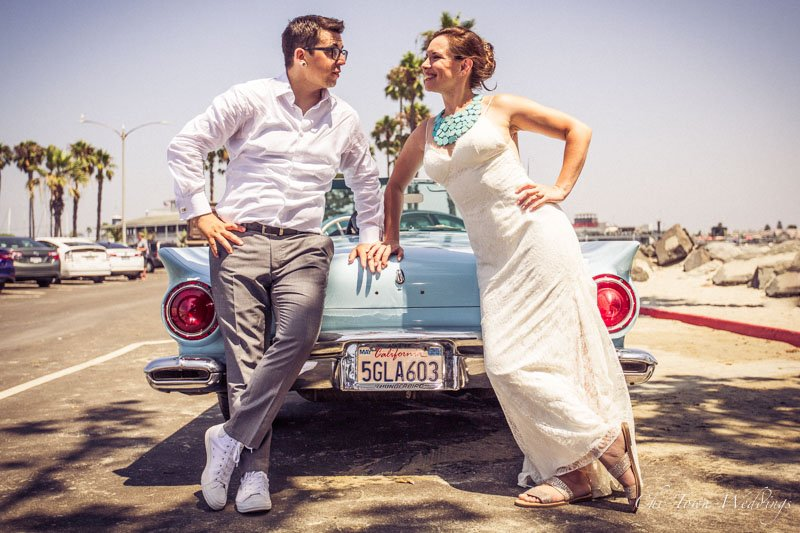 Bride and Groom posing on a convertible