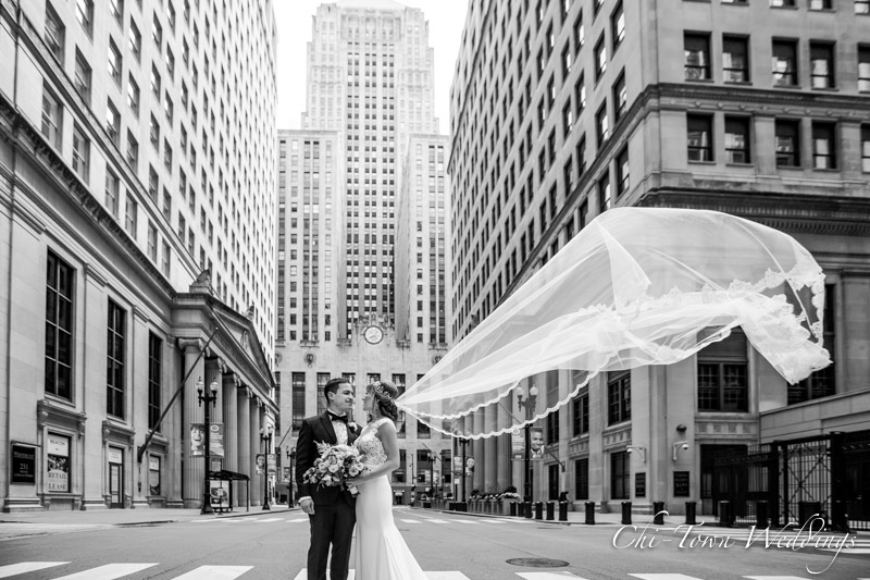 www.Chi-Town-Weddings.com  Bride and Groom Lasalle St Board of Trade Vail flying in the air Chicago