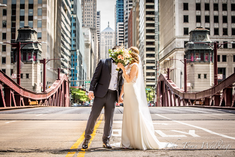 www.Chi-Town-Weddings.com Bride and groom hiding behind flowers Lasalle st chicago