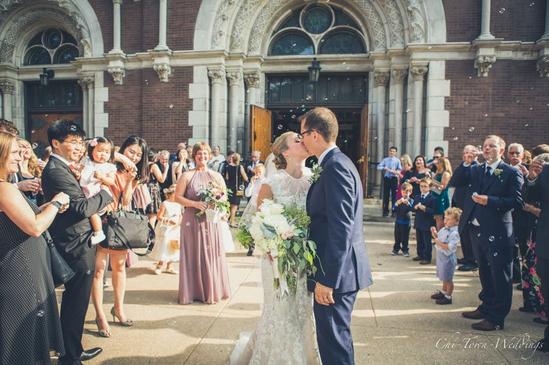 Bride and Groom kissing after the church exit with bubbles all around them