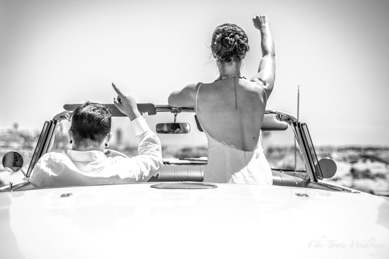 Bride and Groom driving in a convertable